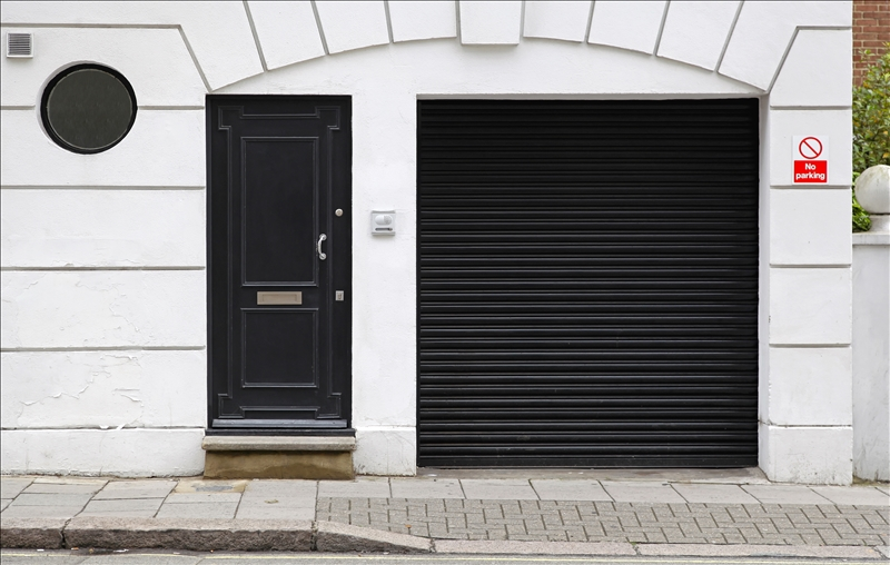 Black garage and entrance door at white house